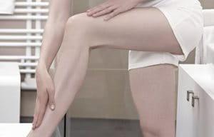 Mujer aplicándose Loción en la pierna.