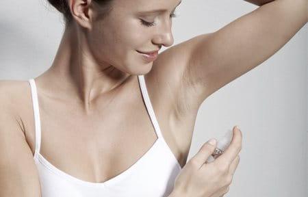 Mujer aplicándose Desodorante Piel Sensible Spray 24h en la axila