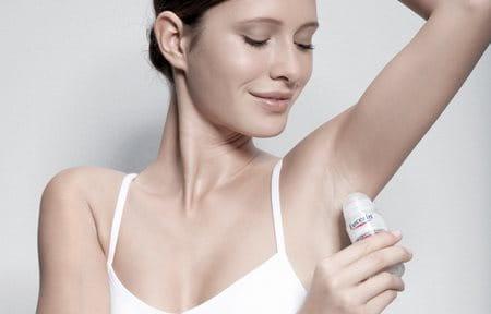Mujer aplicándose Eucerin Desodorante Piel Sensible Roll-On 24h en la axila