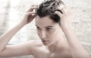 Mujer aplicándose un masaje en el cuero cabelludo húmedo
