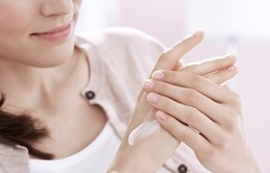 Mujer aplicándose crema de la mano