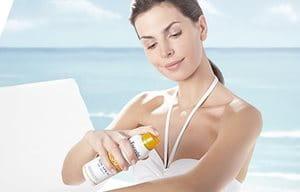 Mujer aplicándose spray solar